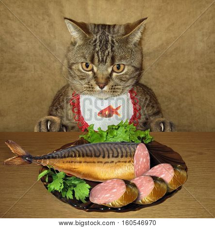 The cat is sitting at the table. There is a fish on a plate. The fish looks like a sausage.