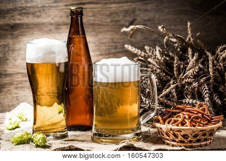 Mug, glasse, bottle of beer with foam on wooden background with wheat spikelets, hops and basket of pretzels