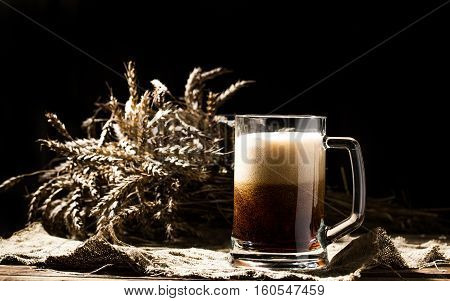 Mug beer with wheat on linen cloth on wooden table