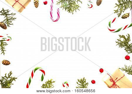 Christmas composition on white background. Xmas gift, green thuja twigs, pine cones and red wild rose fruits. Top view, flat lay. Winter holidays concept