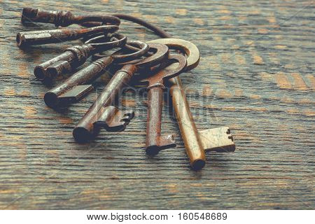 A bunch of old keys on a wooden board
