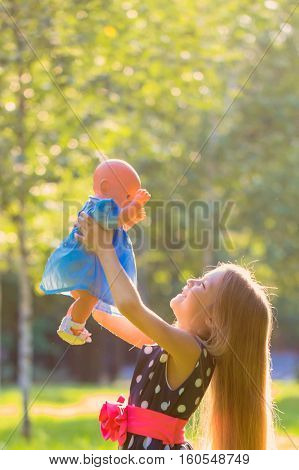 Little girl with doll. Girl playing like mother and daughter
