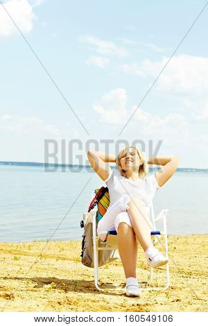 Senior woman resting in chaise lounge on the beach