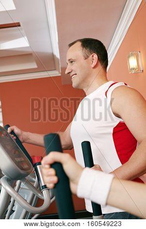 Mid adult man training running in gym