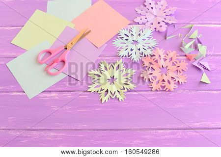 Pink, green, blue and purple paper snowflakes. Paper snowflake set, colored paper sheets and scraps, scissors on wooden background. Kids winter crafts