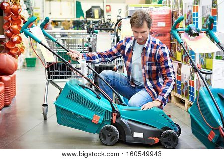Man Chooses Lawn Mower In Store