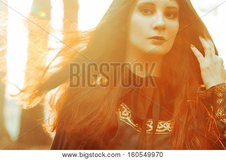 Young beautiful and mysterious woman in the woods, in a black cloak with a hood, the image of a forest elf or witch