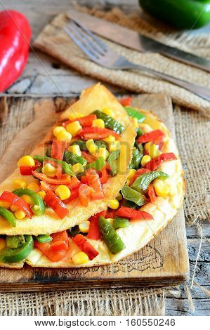 Vegetable omelet on a wooden board. Delicious fried omelet stuffed with red and green bell peppers and corn. Simple vegetarian breakfast omelet recipe. Vintage style. Closeup