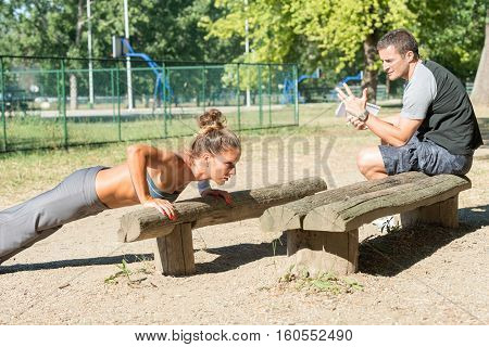 Personal fitnes trainer counting push ups, toned image