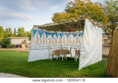 Jewish Holiday Sukkot. The sukkah - symbolic temporary hut fabric sukkah with table and chairs top covered with palm branches