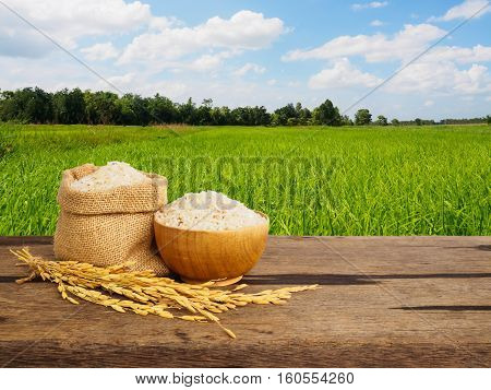 Jasmine rice in sack and bowl on wooden table of rice plant background with copy space