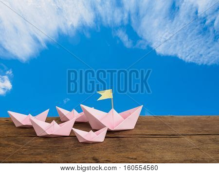 Travel concept and leadership concept paper pink boat group on wooden table with blue sky and copy space