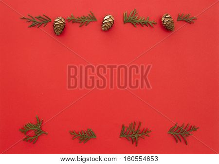 Christmas frame made of green thuja twigs and cones on red background. Top view, flat lay. Copy space for text. Winter holidays concept