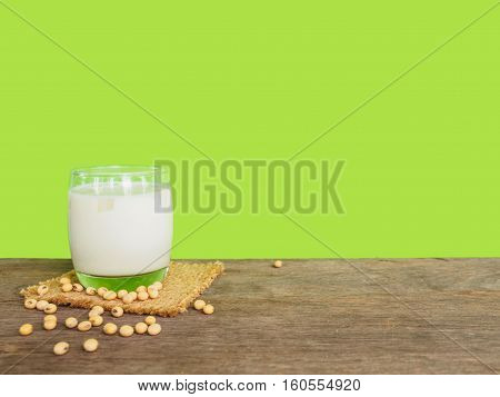 Milk in glass and soy bean on wooden table of green color background with copy space