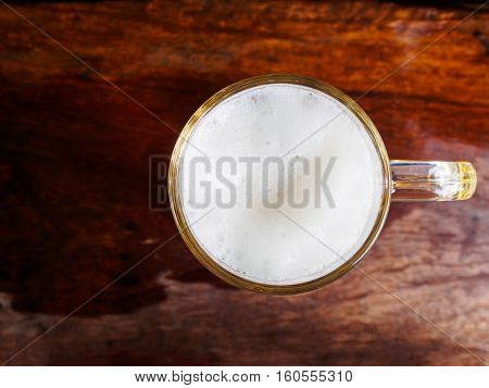 Top view ligh of beer glass on wooden table