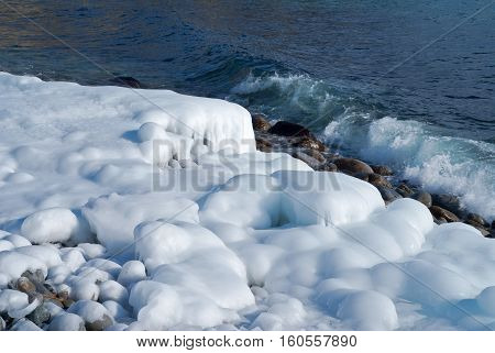 Winter on sea: stones with ice seawater and surf.