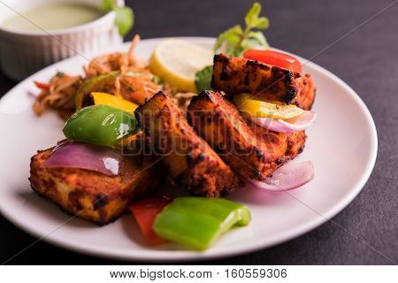 Paneer Tikka or chilli paneer Kabab - Tandoori Indian cheese skewers, served in white plate with colourful capsicum and onion, with green sauce