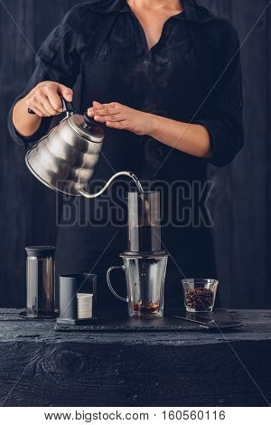 Professional barista preparing coffee alternative method on black background