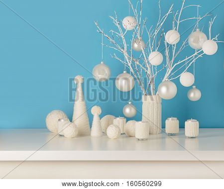 Vase in white knitted cover with white branches and Christmas toys. Candle holders in knitted covers with candles. Christmas tree made from white yarn.
