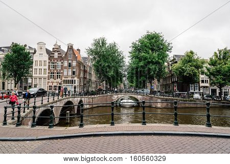 Amsterdam Netherlands - August 2 2016: Street in historical city center of Amsterdam. It is one of the most romantic and beautiful cities in Europe. Amsterdam is also a city of tolerance and diversity.