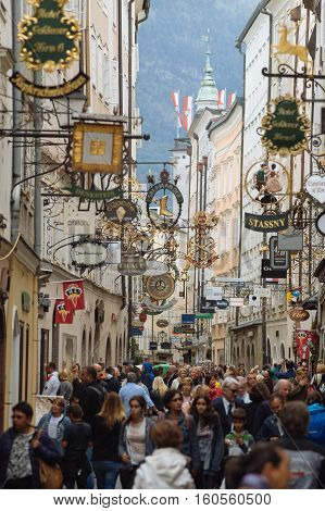 SALZBURG AUSTRIA - AUGUST 21 2016: Famous historical street Getreidegasse with multiple advertising signs. Crowd of people walking and shopping.