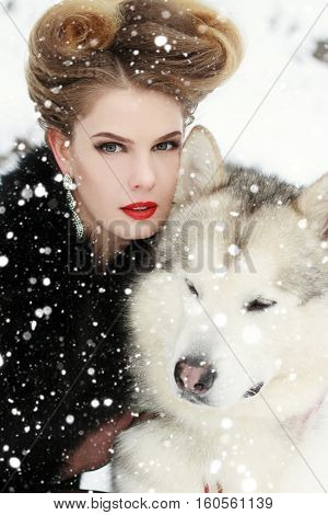 winter christmas animal people beauty concept- Young woman with wolf dog in snow over snow background