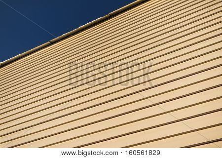 Siding. House siding background. Detail of a house wall. Beige siding and blue sky