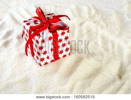 White gift with red stars on a white facture background.