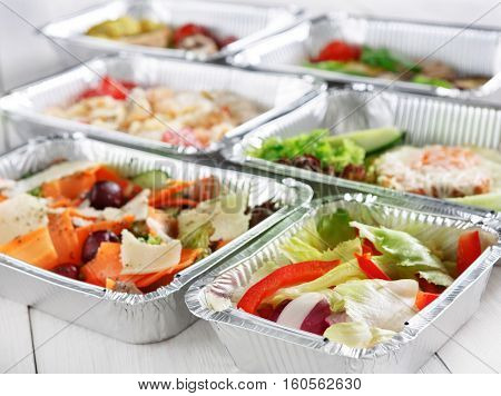 Healthy eating, diet concept. Take away organic food. Weight loss nutrition in foil boxes. Vegetable salads with cheese at white wood