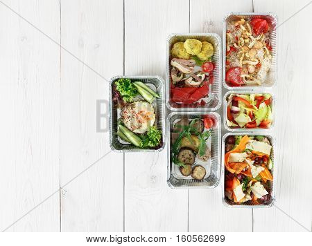 Healthy food delivery. Take away of natural organic fitness dishes for diet. Daily ratio nutrition pyramid meals in foil boxes on white wood. Top view, flat lay