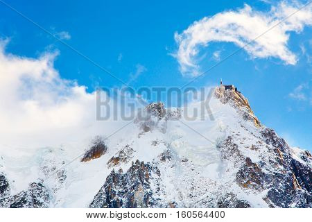 The mountain top station of the Aiguille du Midi in Chamonix, France and ice on the mountains against the blue sky