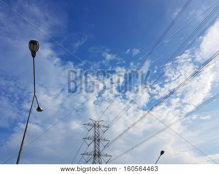 High-voltage tower in cloudy blue sky background with street light pole.