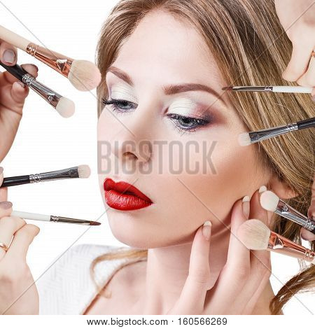Many hands with cosmetics brushes applying make-up to glamour woman.
