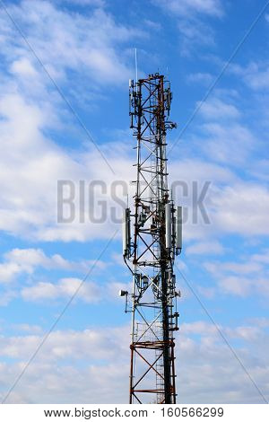 communication tower with mobile telephone antenna on cloudy sky background