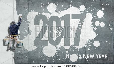 Building painter hanging from harness painting a wall with the words Happy New Year 2017