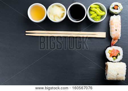 Typical asian cuisine set on black kitchen slate plate. Ginger Japanese horseradish wasabi soy and fish sauce in small white bowls. Chopsticks. Sushi - futomaki and nigiri. Copy space in the bottom left corner.