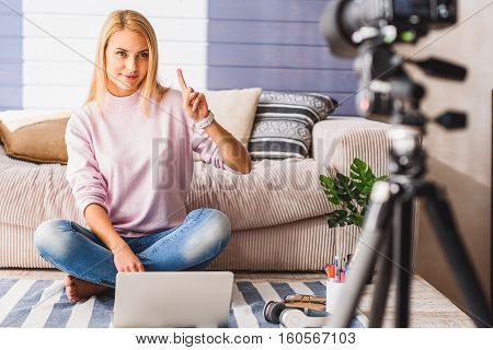 One more advice for you. Pretty young female blogger is pointing finger up and looking at camera with confidence. She is sitting on floor in her apartment and smiling
