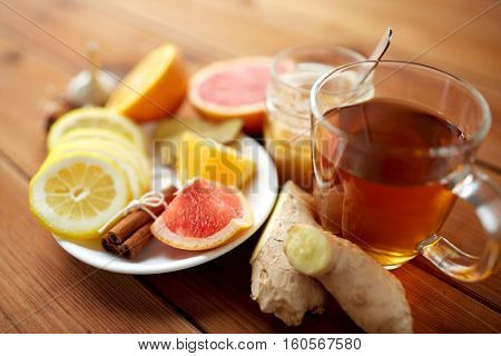 health, traditional medicine, folk remedy and ethnoscience concept - cup of ginger tea with honey, citrus and cinnamon on wooden background