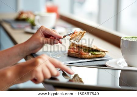 food, dinner, technology and people concept - woman with tablet pc computer eating salmon panini sandwich at restaurant