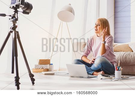 Listen to me attentively. Confident young female blogger is telling important things to camera. She is pointing finger up and smiling