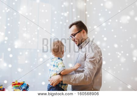 family, parenthood, fatherhood nd people concept - father taking care of little son at home over snow