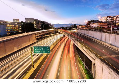 Light streaks over highway, exits and on ramps in downtown, Honolulu at sunset