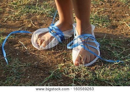 feet of poor girl covered with handmade shoe