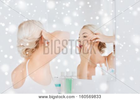 beauty, hygiene, skin problem and people concept - young woman looking to mirror and squeezing pimple at home bathroom over snow