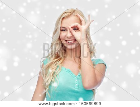 fun, winter holidays and people concept - smiling young woman or teenage girl making ok hand gesture over snow
