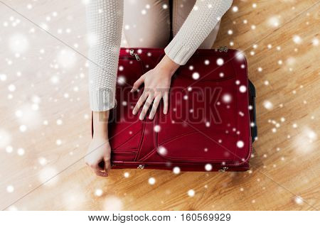 winter holidays, baggage, tourism and people concept - close up of woman packing and zipping bag for vacation over snow