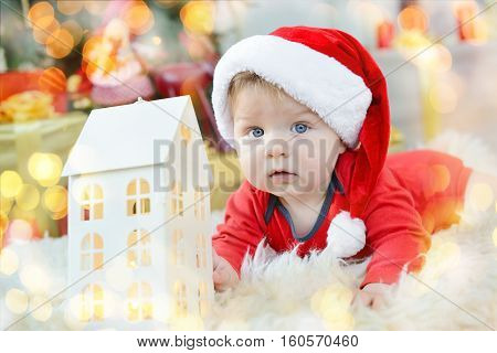 Portrait Of Beautiful Little Baby Celebrates Christmas. New Year's Holidays. Boy In A Santa Costume