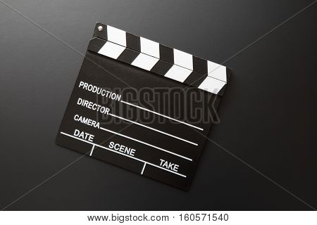 Classic movie clapperboard on black background. Top view.