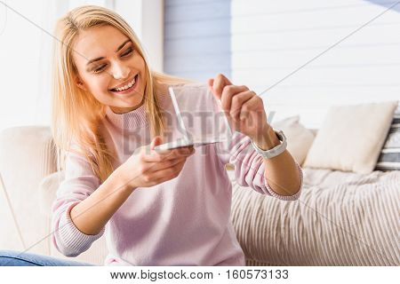 Carefree blond girl is satisfied with make-up product. She is opening set of eyeshadows and looking at it with happiness. Lady is sitting and smiling