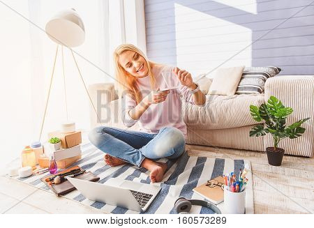 I like online shopping. Joyful young woman is holding blusher and smiling. She is sitting on floor near laptop and other cosmetic products